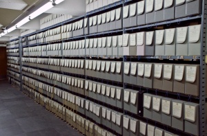 A row of fibredex boxes in the State Records Center. One of our standard records storage cartons equals 1 cubic foot and one of the archival fibredex or Hollinger boxes equals 0.4 cu. ft.