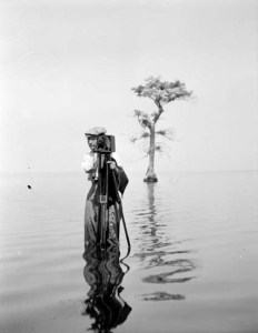 Photographer Bayard Wootten with camera in front of cypress tree in Great Lake, Craven County, NC, 1909