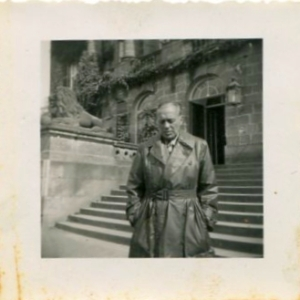 Snapshot of comedian Jack Benny, wearing a leather trench coat, pictured standing in front of the steps of Schloss Wilhelmshöhe