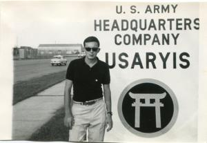 Photograph of Grover M. Johnson Jr. standing next to the sign for Headquarters Company, U.S. Army Ryukyu Islands, ca. 1968