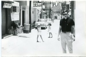 Photograph of Grover M. Johnson Jr. standing in an alley behind some buildings in an unidentified city.