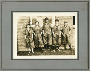 A group of five young women wearing work overalls and caps, standing outside in front of a building at the Wiscassett Mills in Albemarle, N.C. These women replaced male mill workers sent to fight in World War I. (Call number: WWI 2.B11.F7.1)