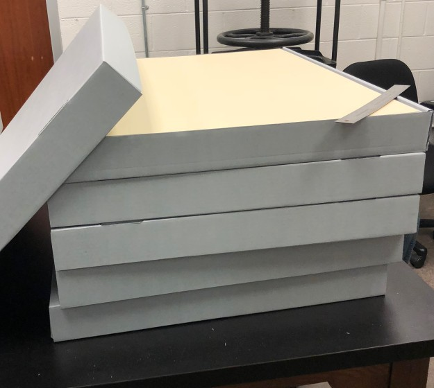 Figure 5. Five boxes are stacked on a table. The top box's lid is removed, so the contents (the completed sink mats) are visible. A ruler is included for scale: the boxes are 25 inches by 32 inches.