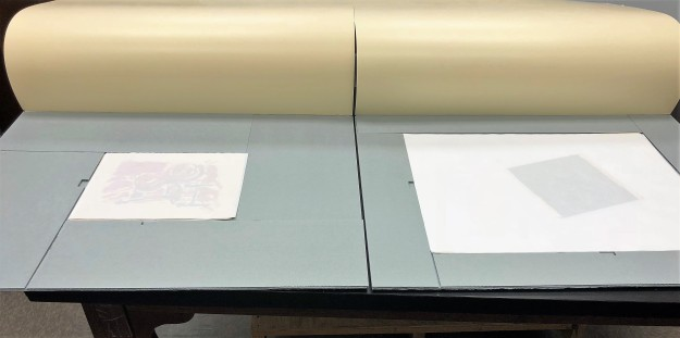 Figure 4. Two completed sink mats of the same size are placed next to each other. One holds a small set of drawings (about 9 inches by 12 inches) and the other a large set (about 19 by 23 inches), demonstrating how mats are custom built to different drawings.