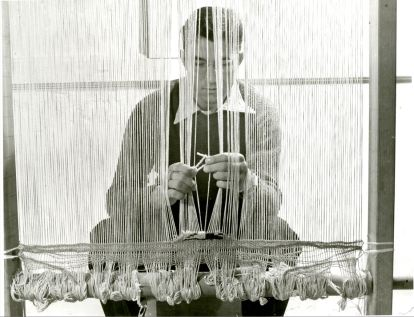 Don Page, a young man wearing glasses, sits at a vertical loom, weaving. The picture is taken through the warp threads of the loom.