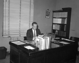 H.G. Jones behind a desk with books and papers on it. A typewriter sits on his left and a bookshelf stands against the far wall