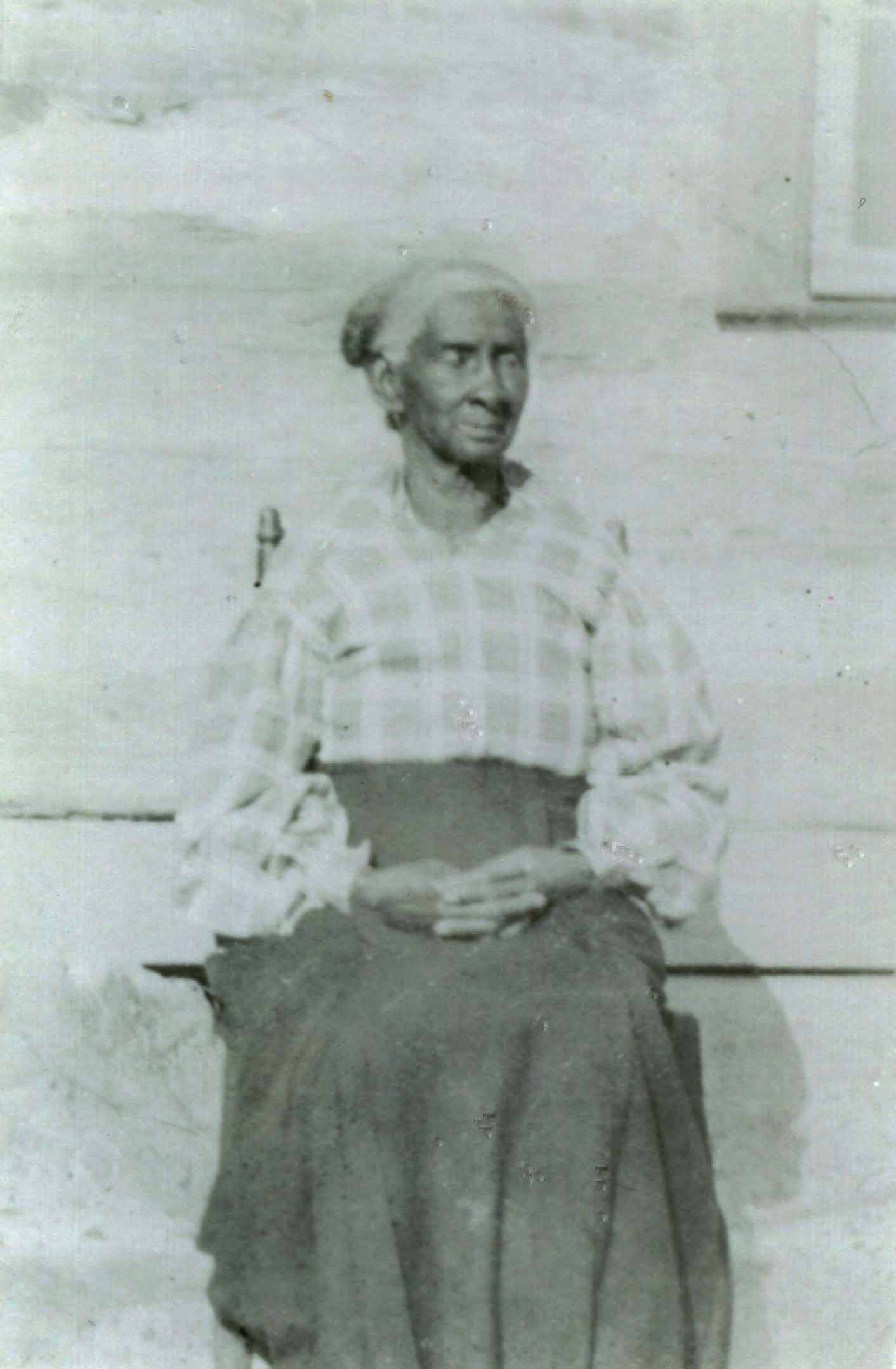 Photo of an African American woman sitting in a chair with her hair up in a bun. she is wearing a checkered shirt and a long, dark colored skirt.